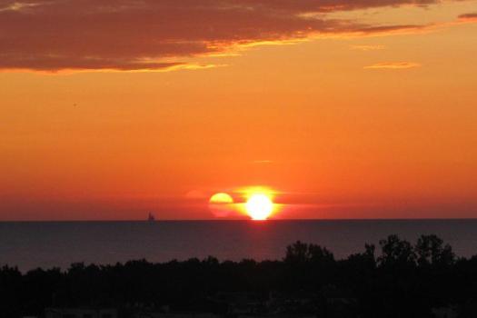 Anómala triple puesta de sol óptica